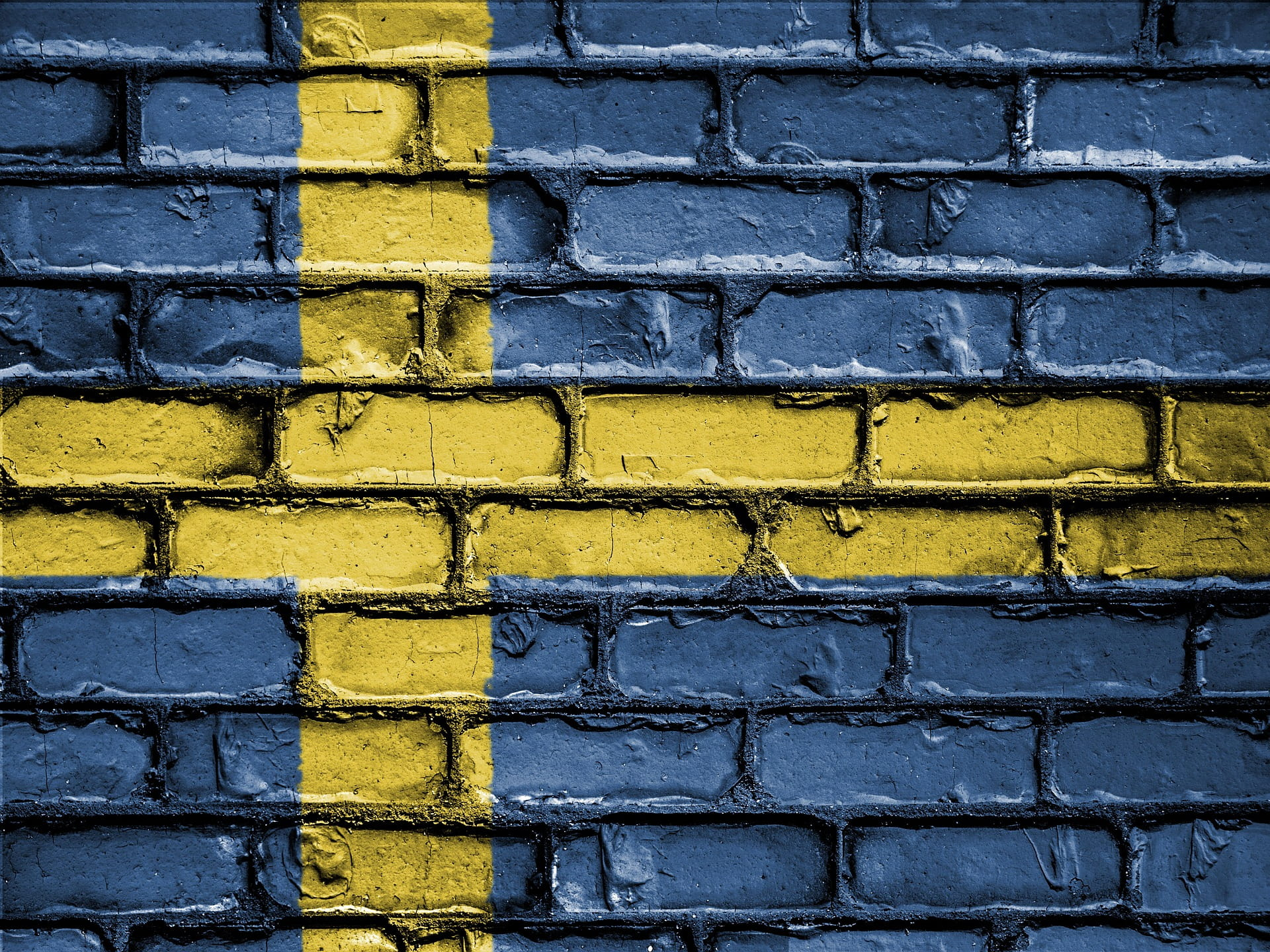 Brick wall painted in the colours of the Swedish national flag.