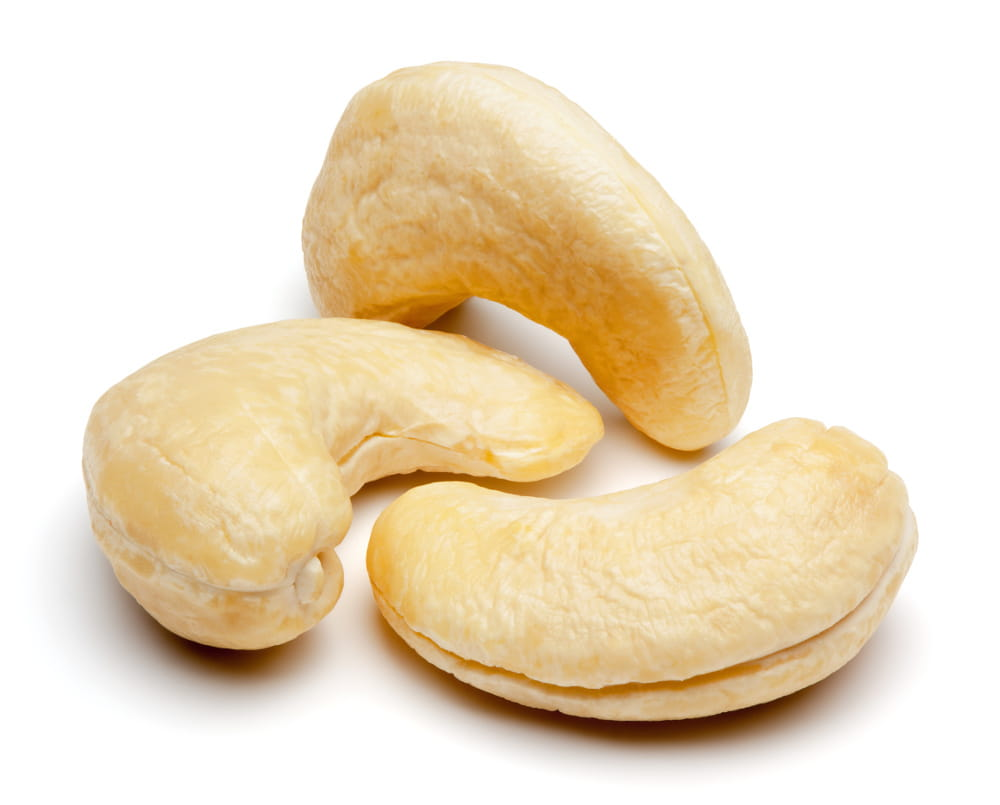 Three cashew nuts on a white background.